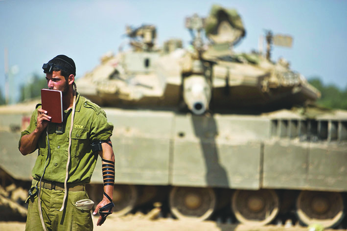An Israeli soldier prays in front of a tank at a staging area near the border with the Gaza Strip