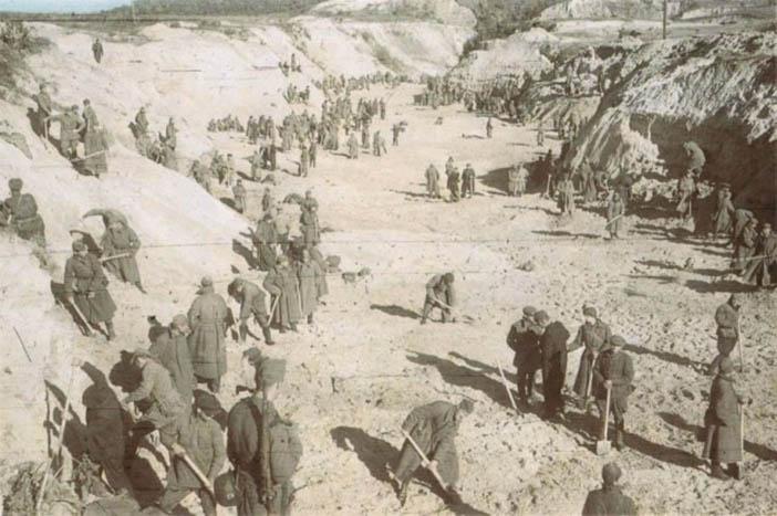 Пленные заваливают тела песком  под конвоем немецких солдат