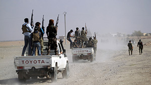 Rebel fighters drive their vehicles as they advance towards Azaz city