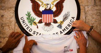 Палестинцы размещают футболку с логотипом, представляющим их заявку на государство, под вывеской консульства