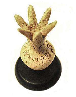 Костяное изделие в форме граната с надписью.