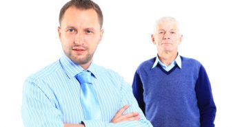 Portrait of a relaxed son standing with his father behind against white background
