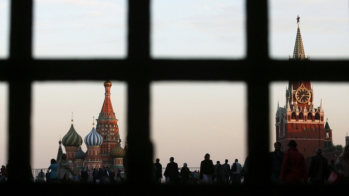 Red Square, St. Basil's Cathedral and the Spasskaya Tower of the Kremlin are seen through a gate in central Moscow