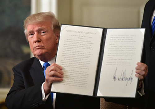 "US President Donald Trump holds up a signed memorandum after he delivered a statement on Jerusalem from the Diplomatic Reception Room of the White House in Washington, DC on December 6, 2017. President Donald Trump on Wednesday recognized the disputed city of Jerusalem as Israel's capital -- a historic decision that overturns decades of US policy and risks triggering a fresh spasm of violence in the Middle East.""I have determined that it is time to officially recognize Jerusalem as the capital of Israel,"" Trump said from the White House.""It's the right thing to do."" / AFP PHOTO / MANDEL NGAN (Photo credit should read MANDEL NGAN/AFP/Getty Images)"