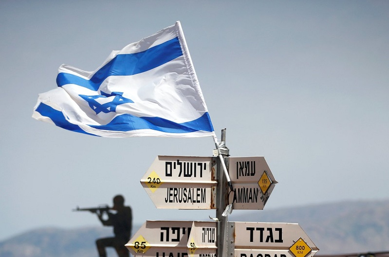 An Israeli soldier stands next to signs pointing out distances to different cities, on Mount Bental, an observation post in the Israeli-occupied Golan Heights that overlooks the Syrian side of the Quneitra crossing