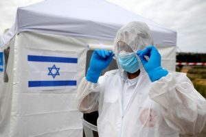 A paramedic adjusts his protective suit as he prepares outside a special polling station set up by Israel's election committee so Israelis under home-quarantine can vote in Israel's national election, in Ashkelon, Israel