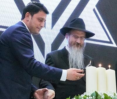 Герман Захарьяев зажигает свечу в день 26 ияра.  Справа: Главный раввин России Берл Лазар