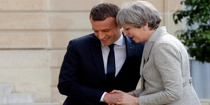 French President Emmanuel Macron greets Britain's Prime Minister Theresa May before a working dinner at the Elysee Palace in Paris