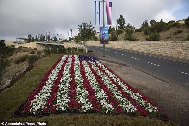 Flowers decorated as an American flag are seen on a road leading to the US Embassy compound ahead the official opening in Jerusalem, Sunday, May 13, 2018. On Monday, the United States moves its embassy in Israel from Tel Aviv to Jerusalem, the holy city at the explosive core of the Israeli-Palestinian conflict and claimed by both sides as a capital. The inauguration comes five months after President Donald Trump recognized Jerusalem as Israel's capital. (AP Photo/Ariel Schalit)