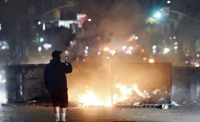 A man films himself in front of a fire in the middle of Melrose Avenue, Saturday, May 30, 2020, in Los Angeles. Protests were held in U.S. cities over the death of George Floyd, a black man who died after being restrained by Minneapolis police officers on May 25. (AP Photo/Chris Pizzello)