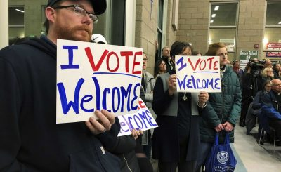 Residents in support of continued refugee resettlement hold signs at a meeting in Bismarck, N.D., Monday Dec. 9. 2019. Several church leaders are urging Burleigh County not to be the nation's first to refuse new refugees since President Donald Trump ordered that states and counties should have the power to do so. (AP Photo/James MacPherson)