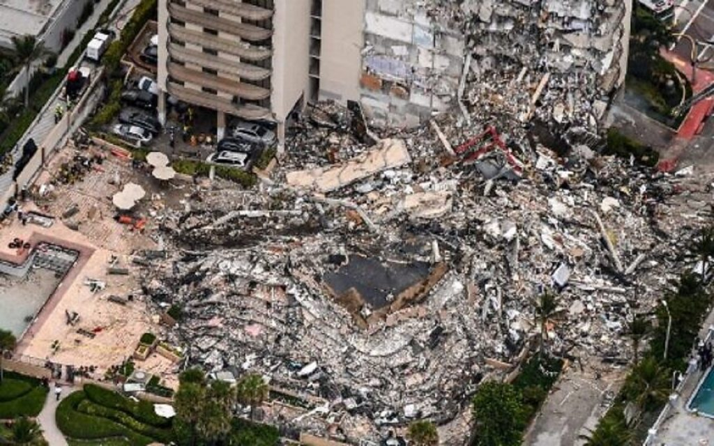 """This aerial view, shows search and rescue personnel working on site after the partial collapse of the Champlain Towers South in Surfside, north of Miami Beach, on June 24, 2021. - The multi-story apartment block in Florida partially collapsed early June 24, sparking a major emergency response. Surfside Mayor Charles Burkett told NBC's Today show: """"My police chief has told me that we transported two people to the hospital this morning at least and one has died. We treated ten people on the site."""" (Photo by CHANDAN KHANNA / AFP)"""