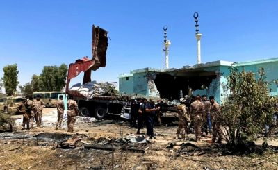 Security forces gather near a destroyed truck used as rocket launcher that sits near a damaged mosque in Anbar, Iraq, Thursday, July 8, 2021. Rockets targeted the heavily fortified Green Zone in the Iraqi capital Baghdad on Thursday, causing some damage but no reported casualties, Iraqi security forces said. (Joint Operations Command Media Office, via AP)